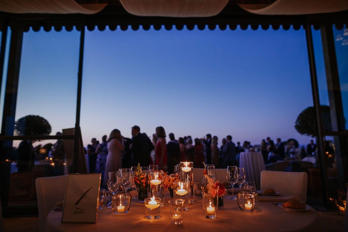 Blick vom gedeckten Tisch auf die Terrasse hinaus mit den Hochzeitsgästen.