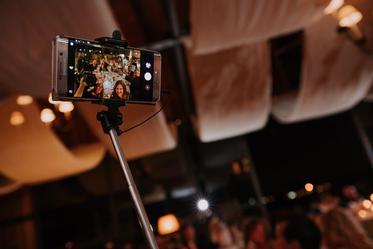 Hochzeitsgäste machen ein Selfie am Tisch.
