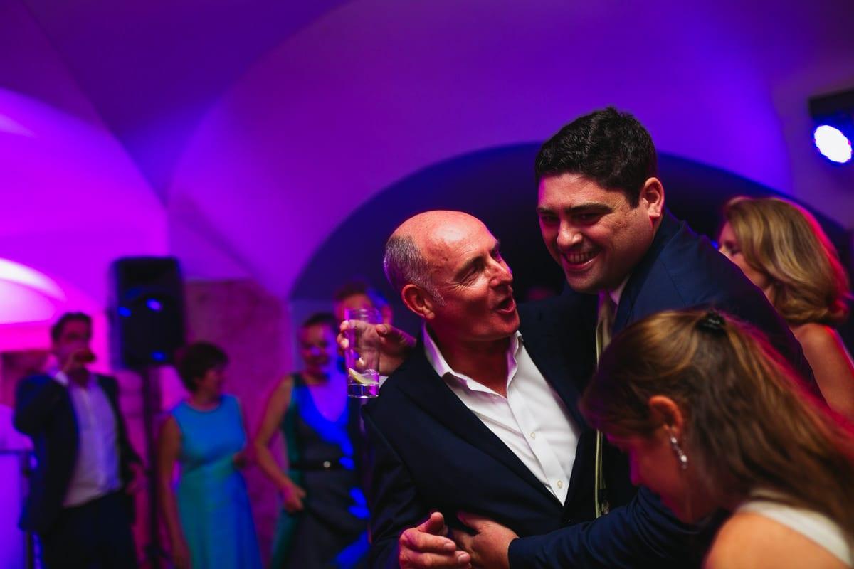 Der Bräutigam in einer Umarmung mit einem Freund während der Party.