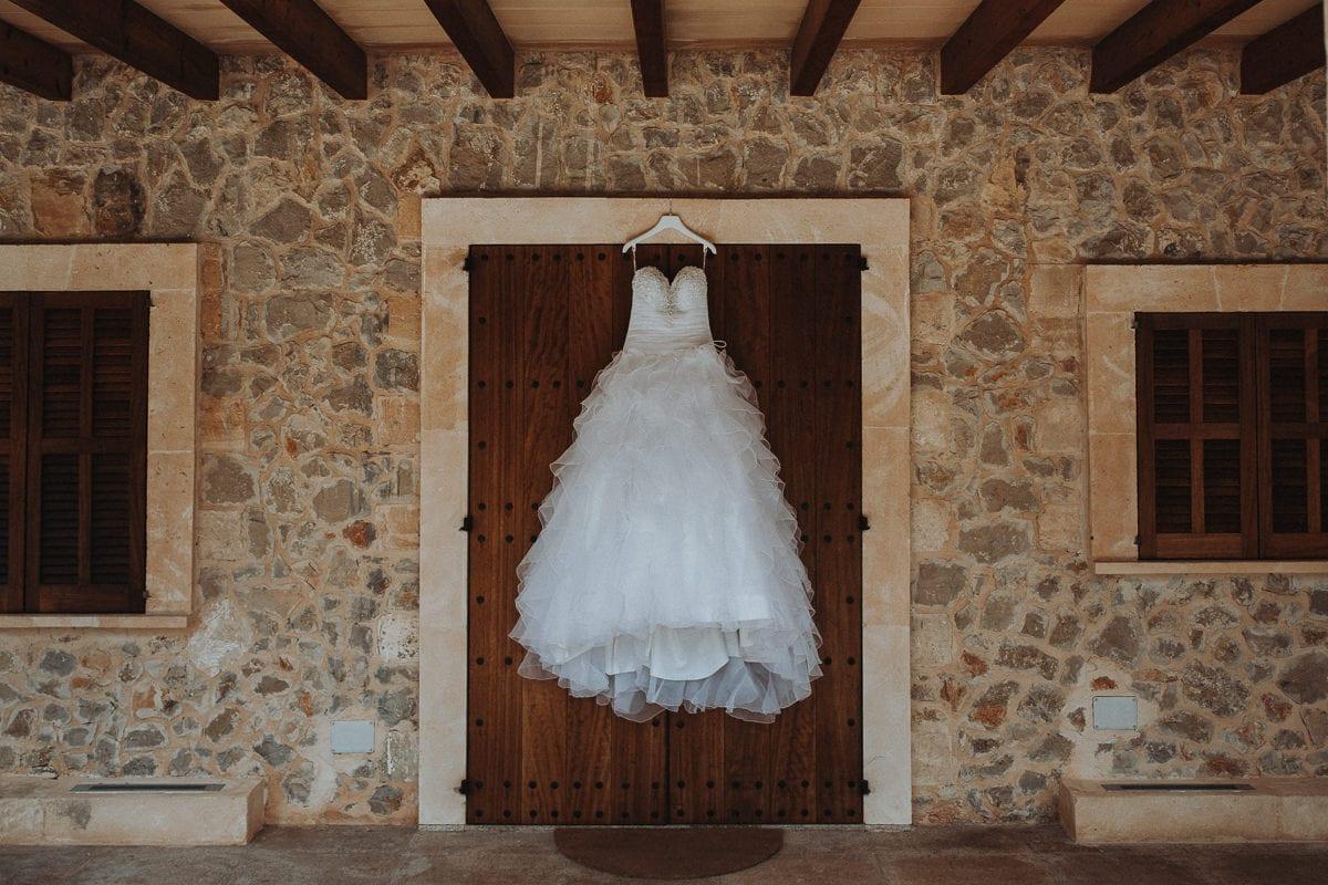 Brautkleid hängt an der Tür der rustikalen Finca Hochzeitslocation Son Burgues