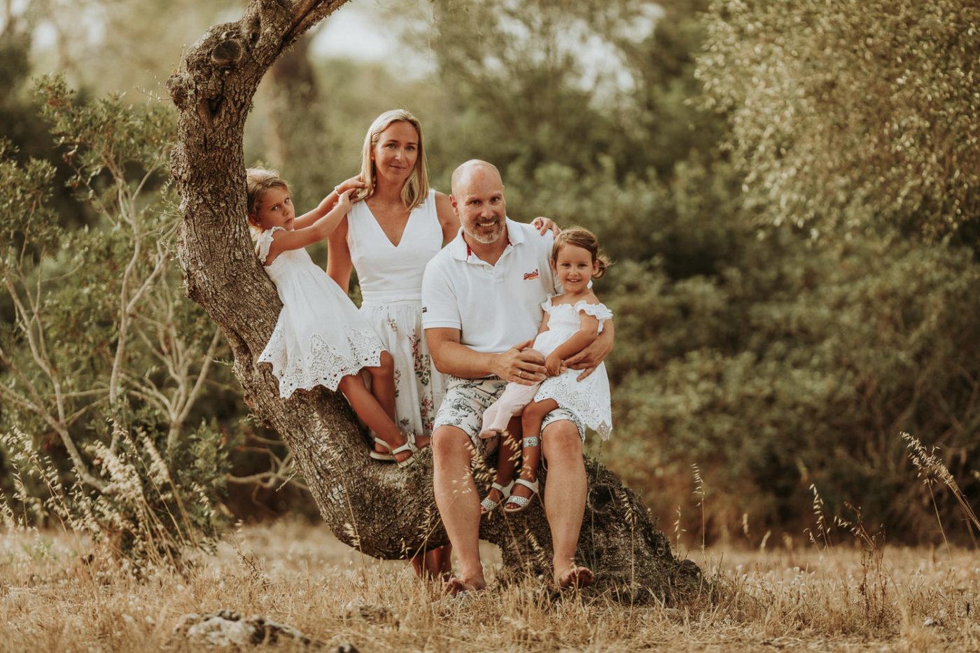 Farbiges Familiengruppenfoto zwischen wilden Olivenbäumen.