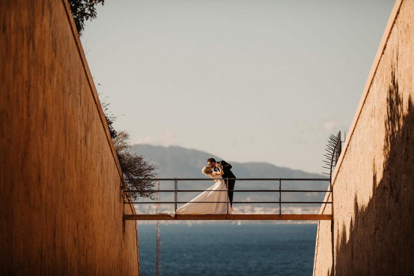 Brautpaarkuss auf der brücke im Cap Rocat mit dem Meer im Hintergrund