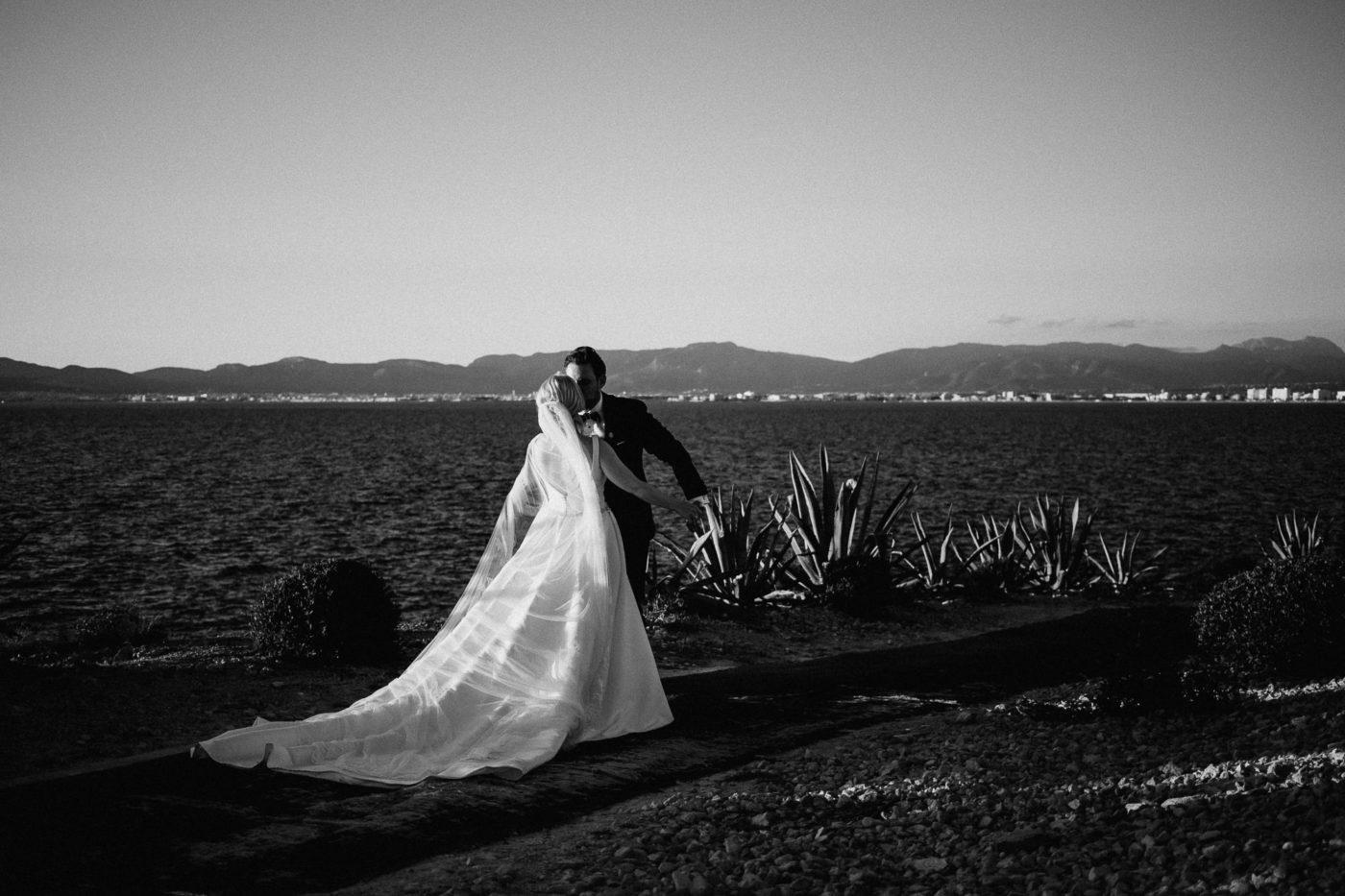 Das Brautpaar küsst sich vor der Meereskulisse