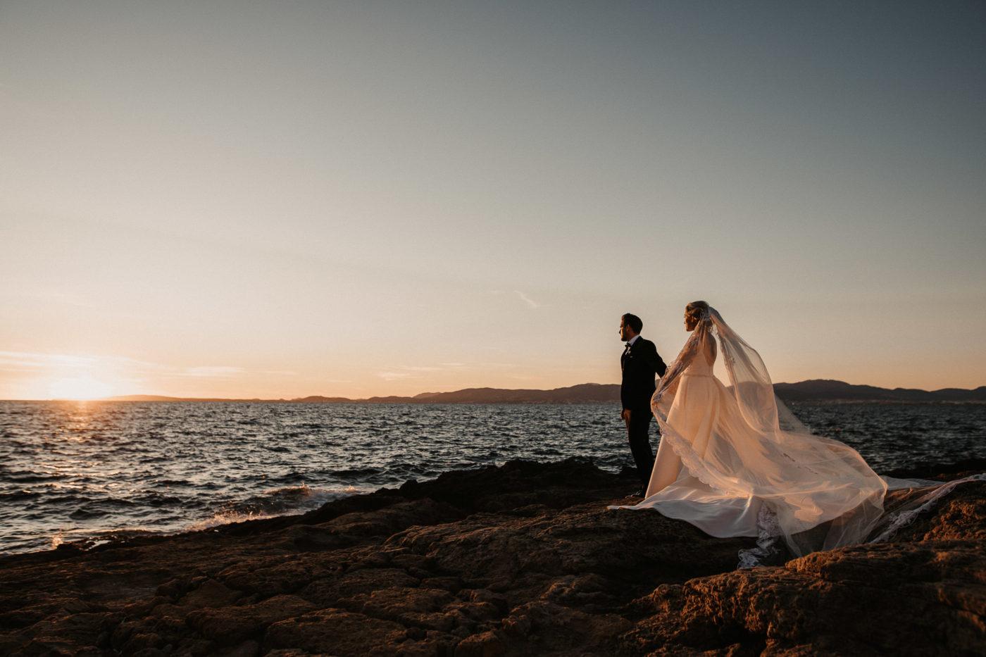 Das Hochzeitspaar zum Sonnenuntergang am Felsenstrand im Cap Rocat