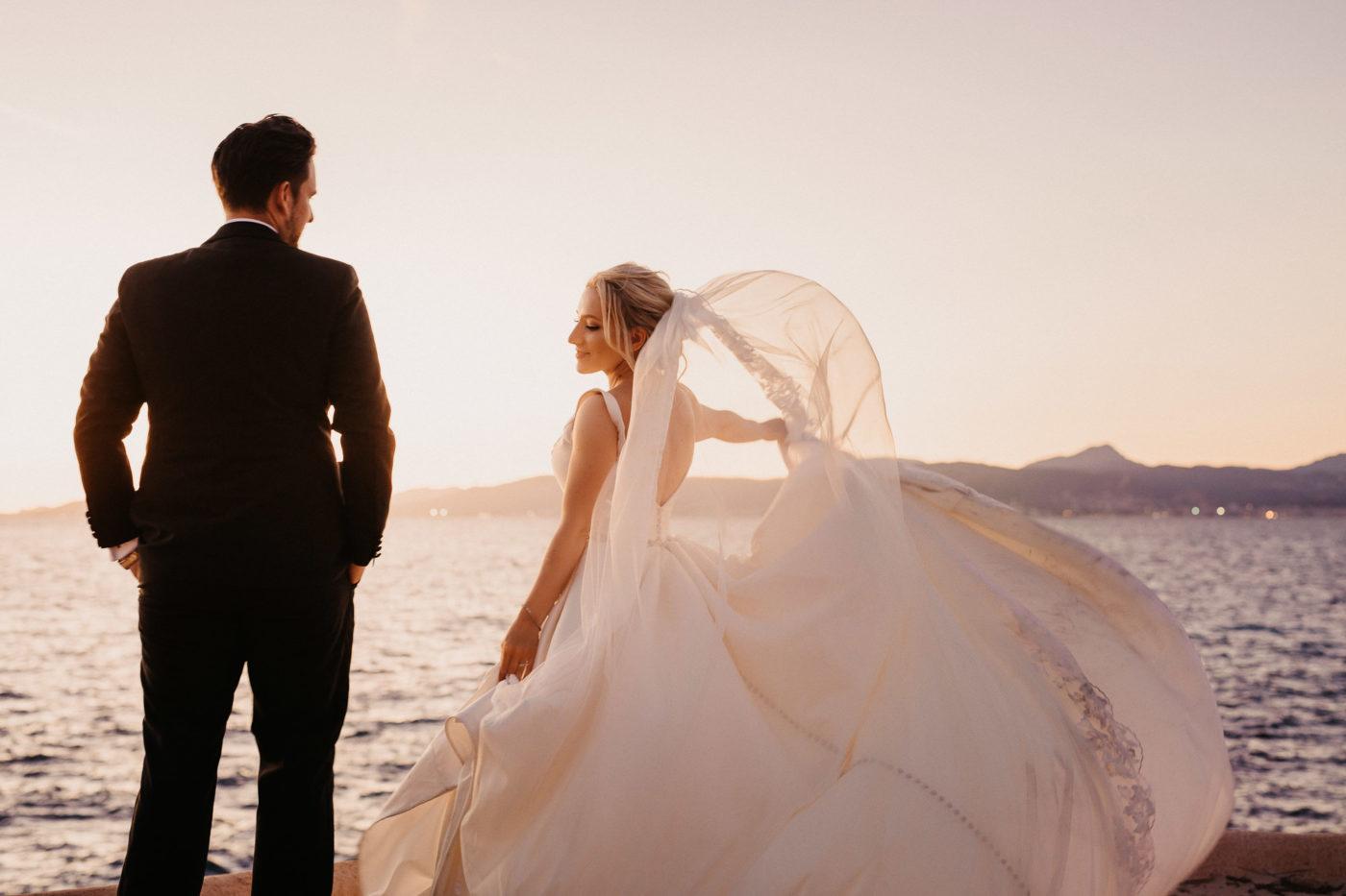 Das Brautpaar am Meer mit eine brise Wind im Brautkleid