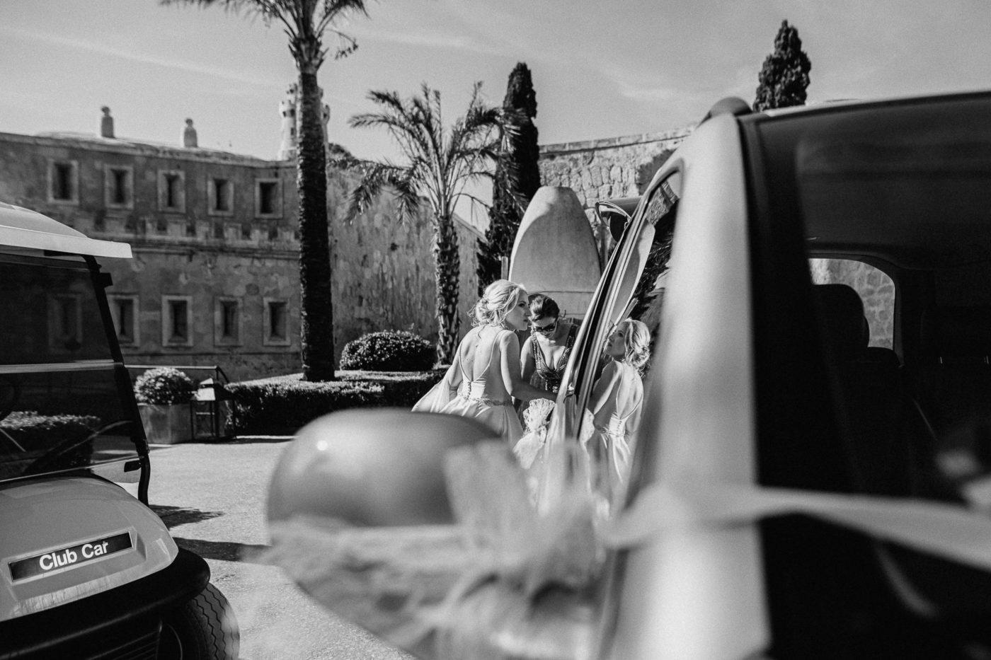 Die Braut mit Spiegelung im Hochzeitsauto am Eingang ihrer Hochzeitslocation auf Mallorca