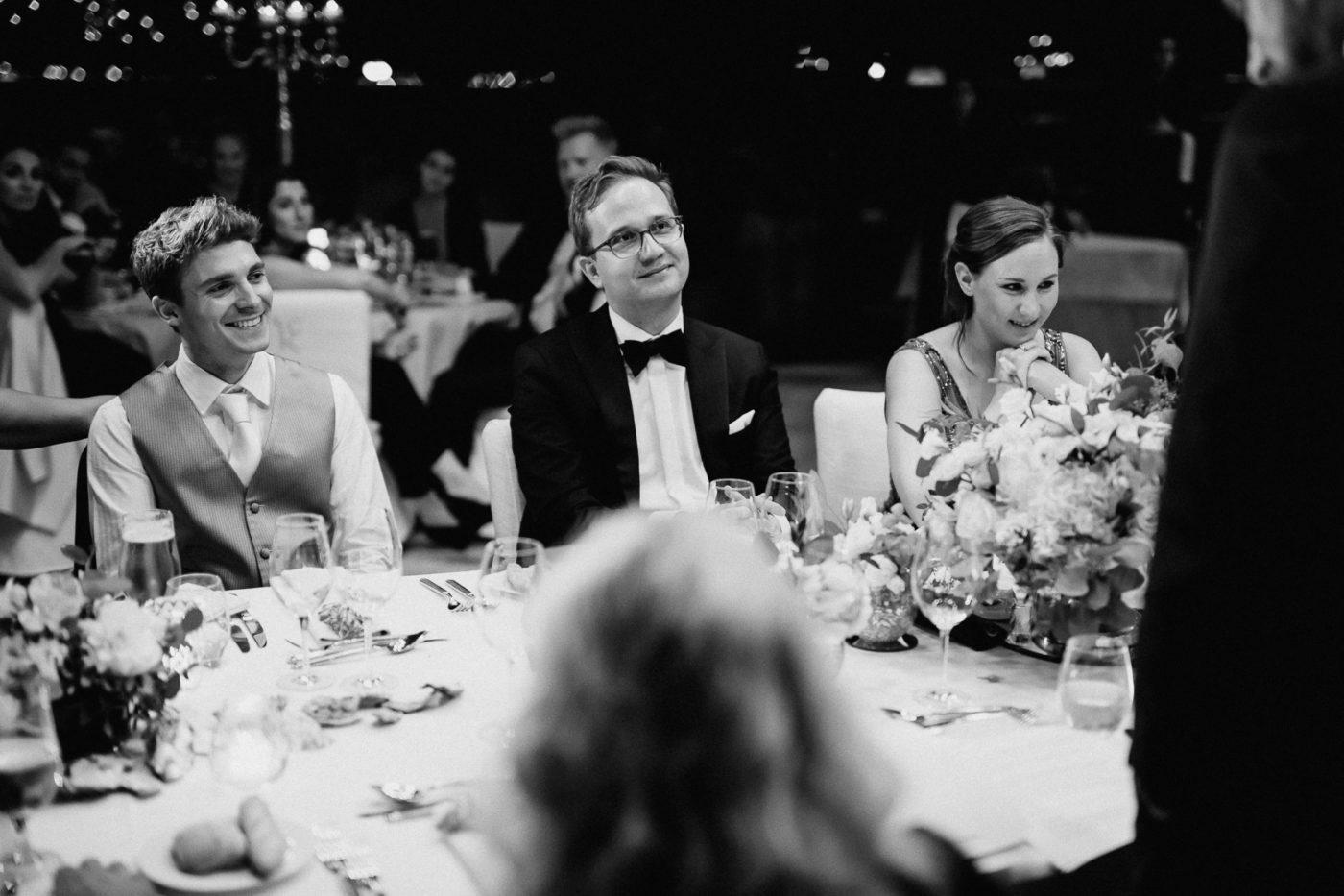 Die lächelnden Gäste hören der Tischrede des Bräutigams zu