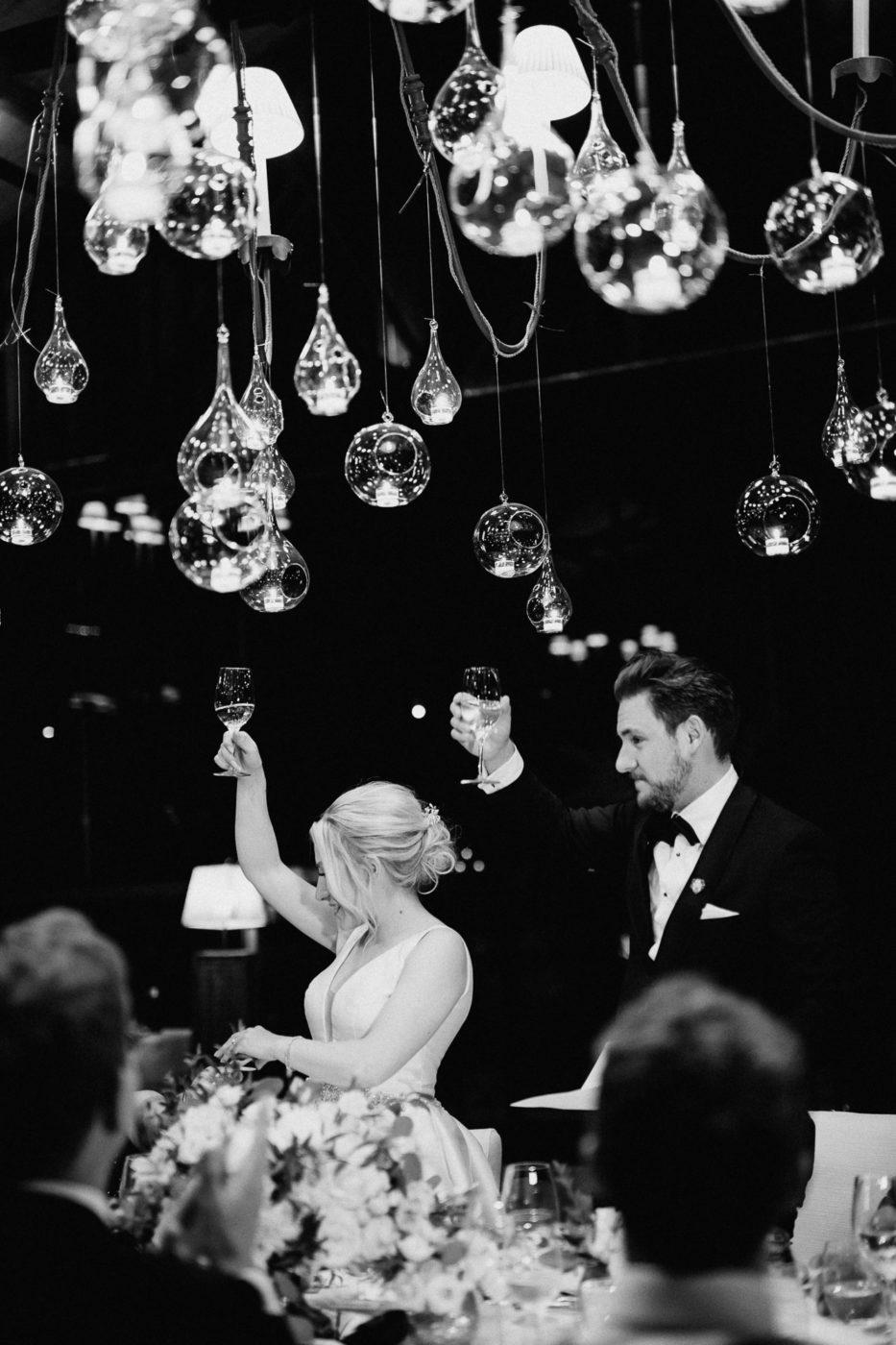Das Brautpaar hebt die Gläser an der Hochzeitstafel