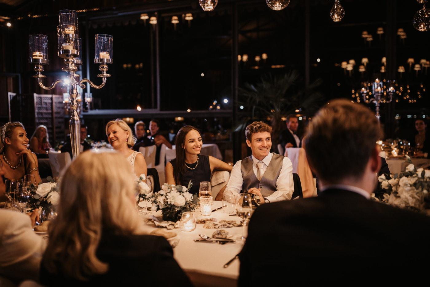 Die Hochzeitsgäste hören lächelnd den Tischreden zu