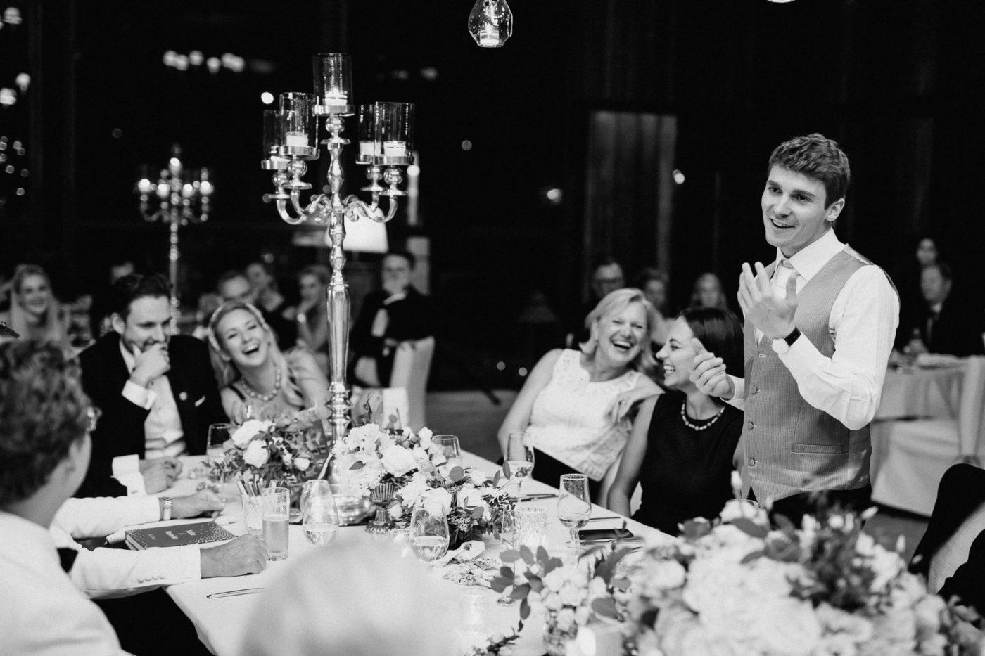 Der Trauzeuge während seiner Tischrede umringt von lachenden Gästen