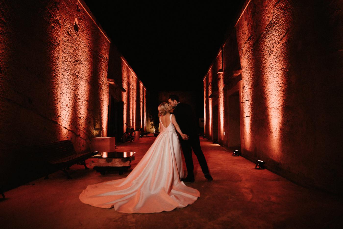 Das küssende Brautpaar zwischen den spektakulär ausgeleuchteten Mauern der Hochzeitslocation Cap Rocat