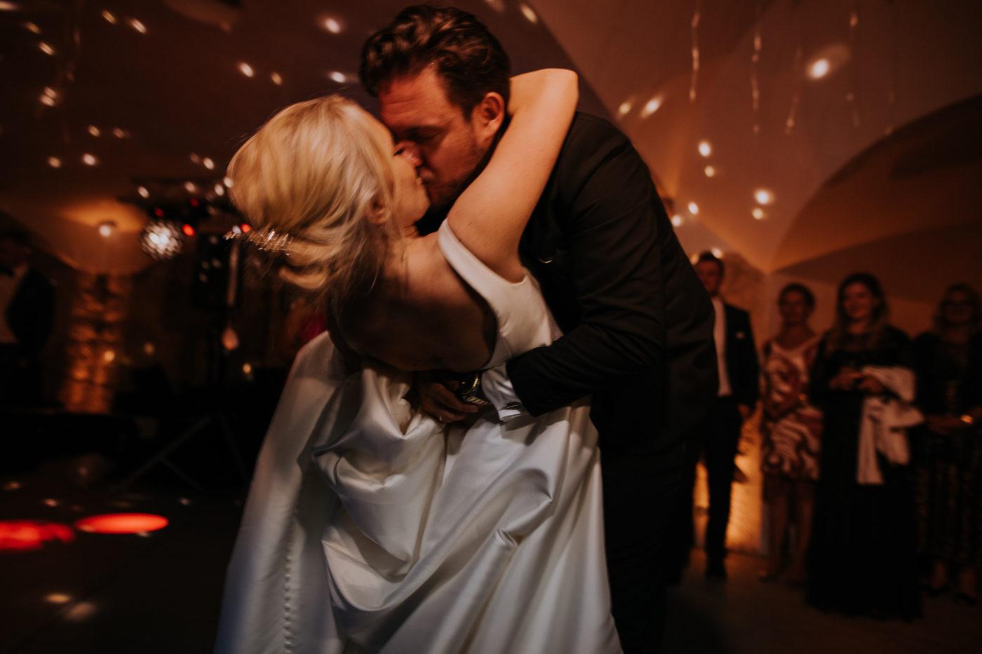 Der Bräutigam küsst seine Braut während des Eröffnungstanzes