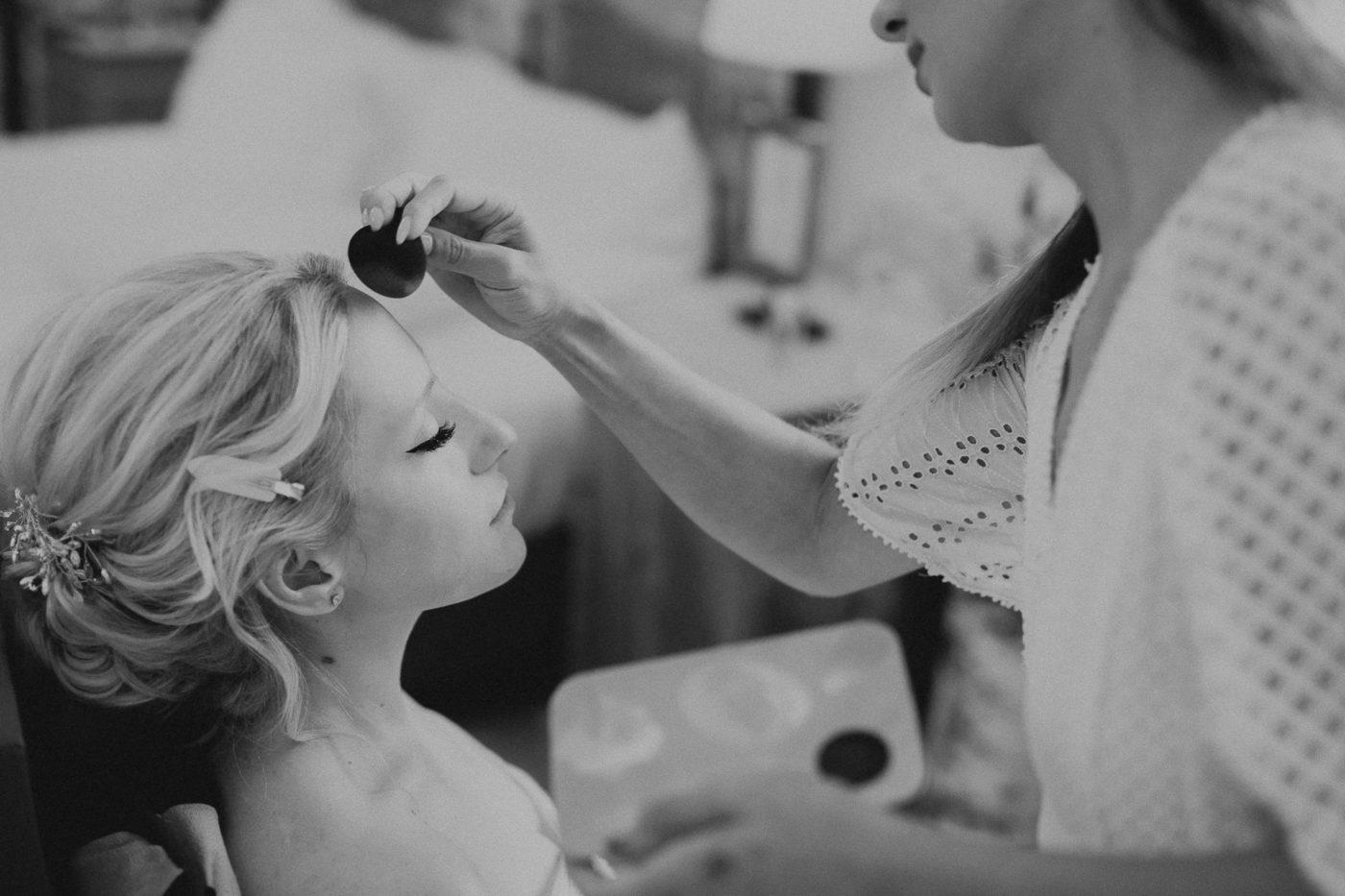 Wunderschönes Foto der Braut während des Auftragen des Make ups