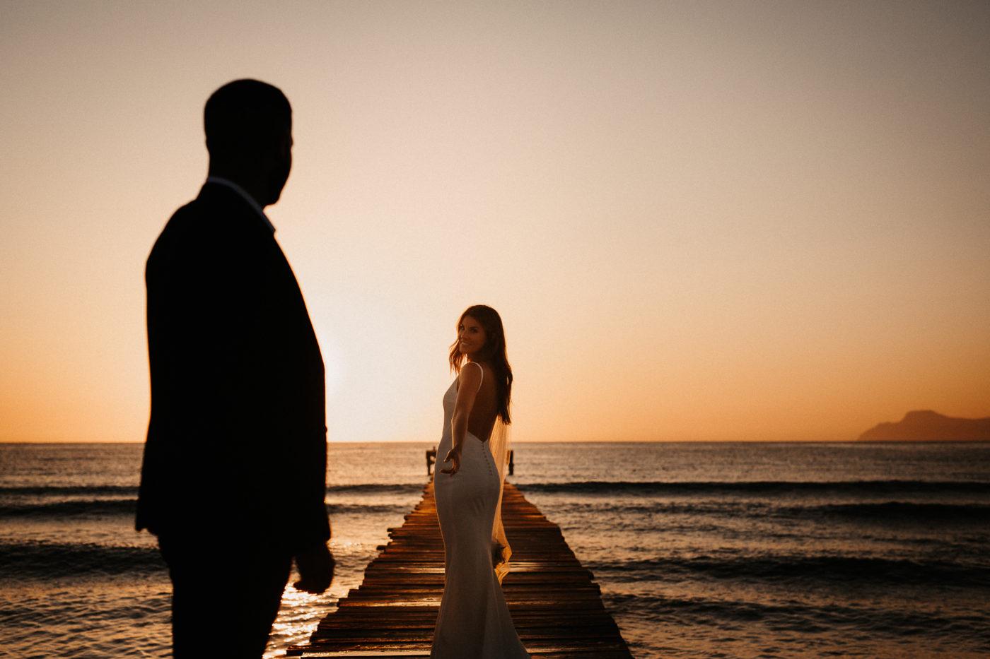 Die Braut reicht ihrem Mann die Hand auf einem Holzsteg am Strand auf Mallorca