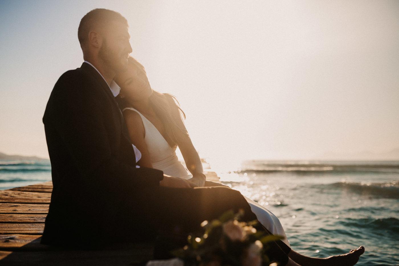 Kuschelndes Brautpaar auf dem Steg sitzend am Meer