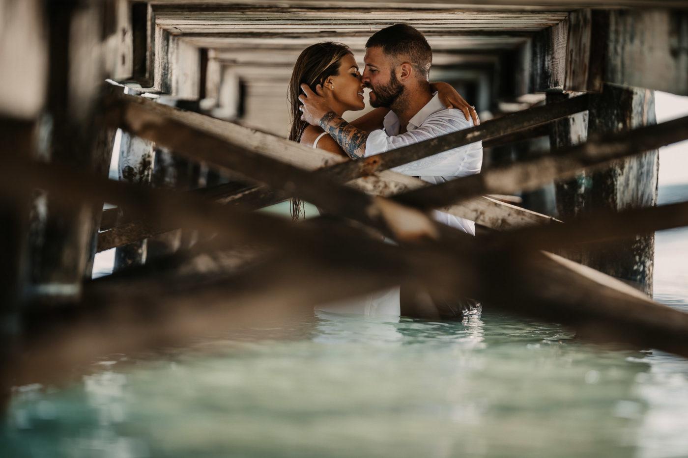 Küssendes Brautpaar im Wasser unterm Steg am Strand