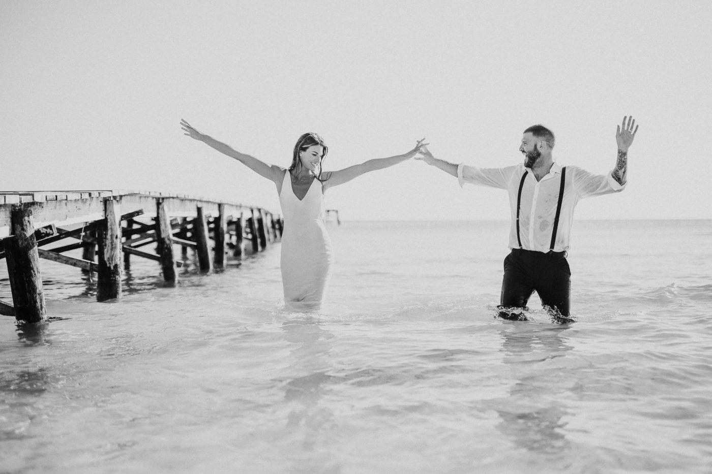 Glückliches Brautpaar mit erhobenen Armen im Wasser im Meer